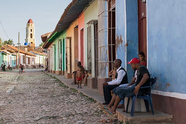 Gens assis sur le trottoir dans une rue de Trinidad (Cuba)