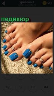Показаны женские ноги с украшениями и педикюром на ногтях синего цвета