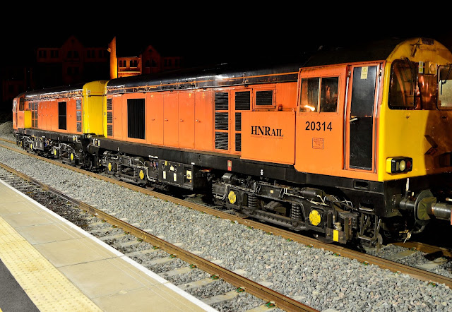 Night Photo of Class 20314 diesel locomotive in HN Rail livery pauses at Banbury railway station while operating a London Underground rolling stock service