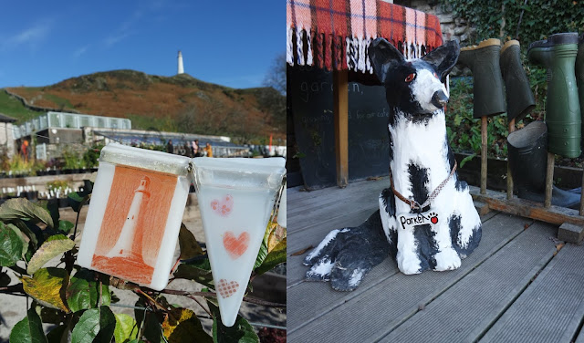 left: a suncatcher showing hoad hill monument, with the real hill and monument in the background behind it. Right: a paper model of a black and white border collie