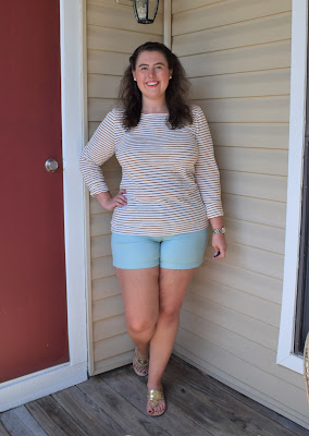 an outfit with a gold striped tee, turquoise shorts, gold sandals, and a gold watch