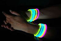 Geceleyin bir bayanın kolunda parlayan çeşitli renklerde fosfor ışıklı bilezikler