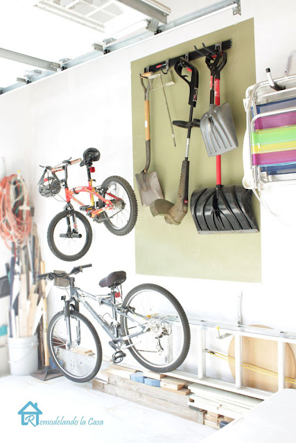 garage wall with storage for long garden tools, bicycles, trimmer and extension cords