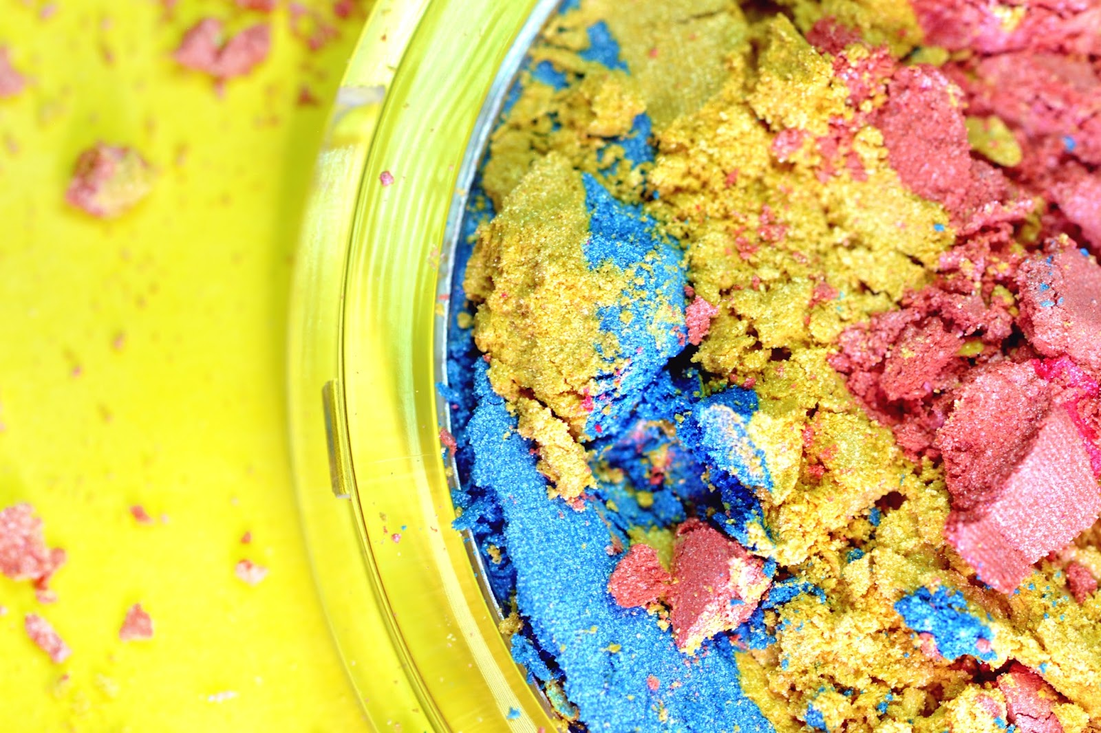 Macro of crumbled rainbow highlighter on yellow background