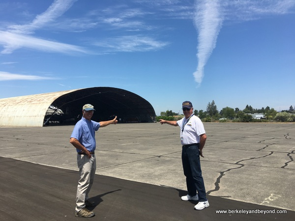 Andy Werback and W. David Ford point to Butler hangar at Pacific Coast Air Museum in Santa Rosa, California