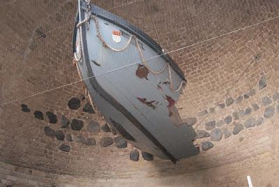 Ein halb zerstörtes Holzruderboot hängt in der Eigelsteintorburg. Es ist grau und an der Spitze ist das kölner Stadtwappen zu sehen.