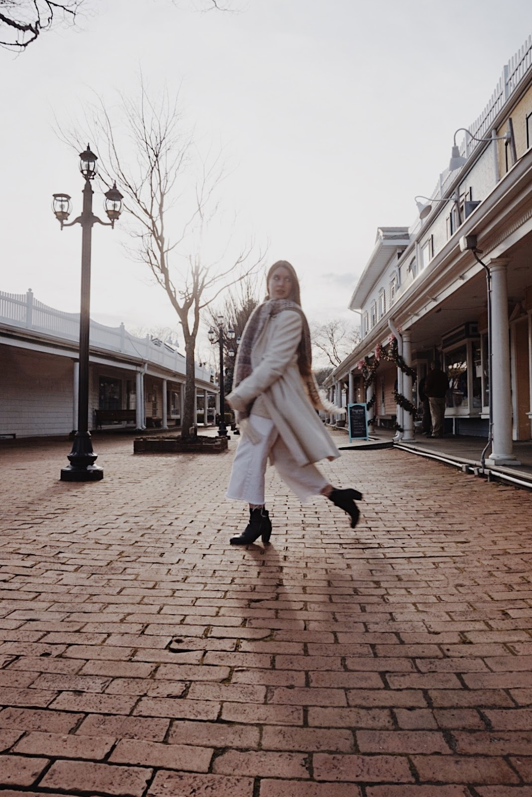 a girl walking a white winter coat and white jeans with scarf