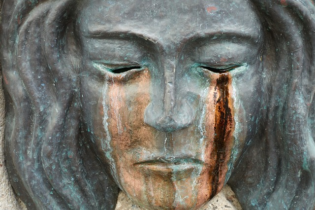 crying face of a stone statue