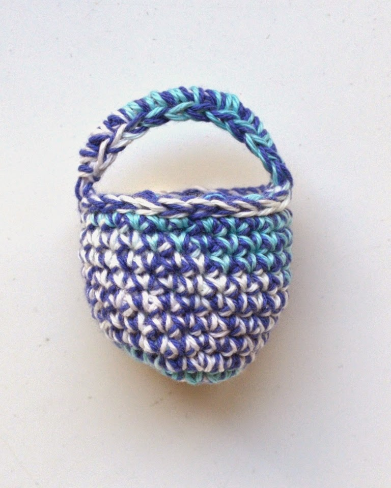Crocheted mini basket with solid navy right through combined with either aqua or white at random according to variegated pattern in aqua/white yarn.