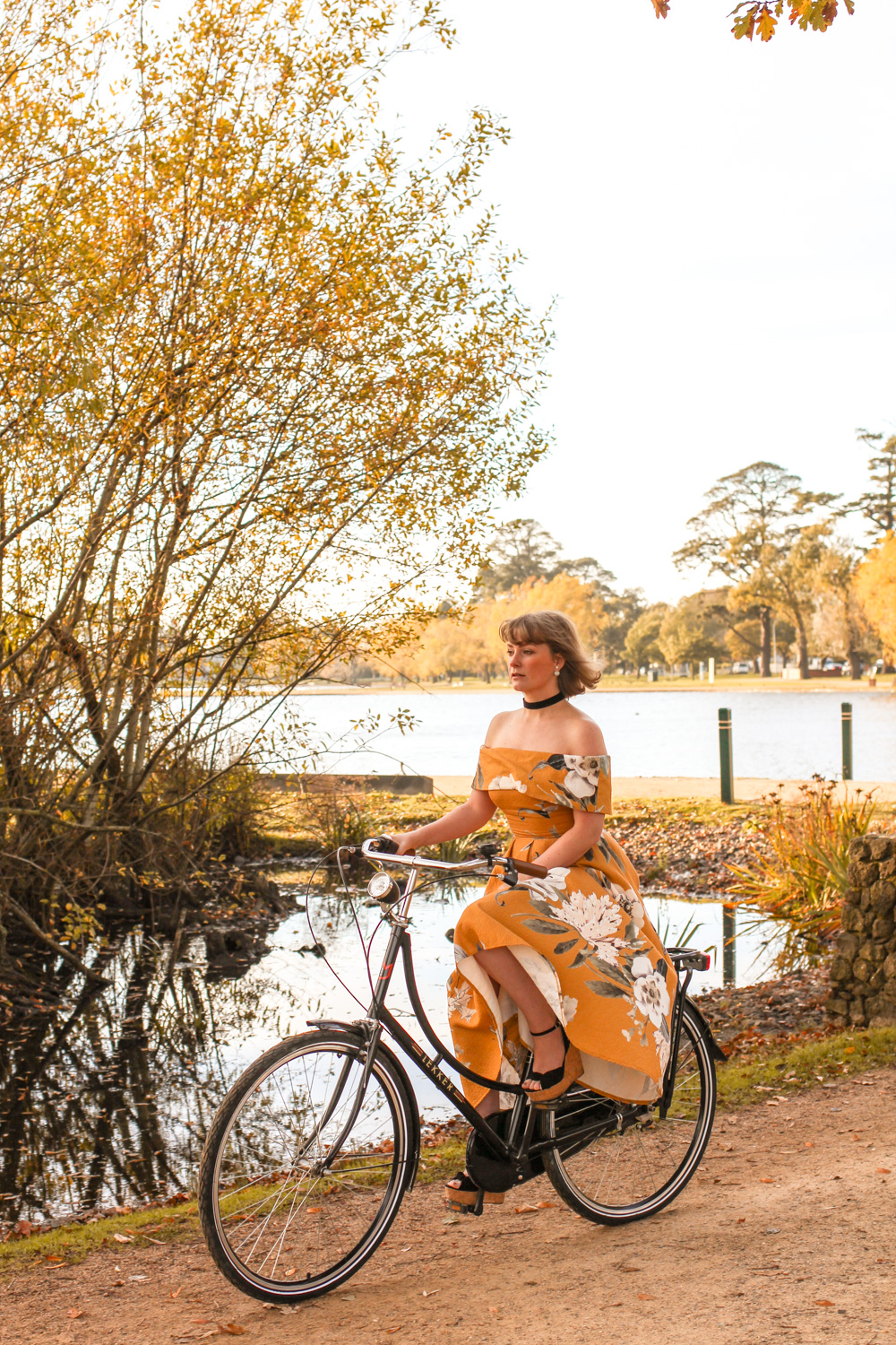 Liana of @findingfemme wearing yellow ASOS off the shoulder dress with black bike