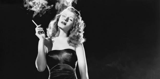 Imagen de Rita Hayworth en un fotograma de GIlda, la femme fatale más popular del cine, se la ve vestida con un vestido largo, negro y muy ajustado