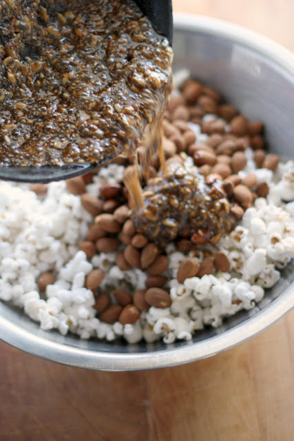 pouring the seeds and spiced syrup over the popcorn and almonds