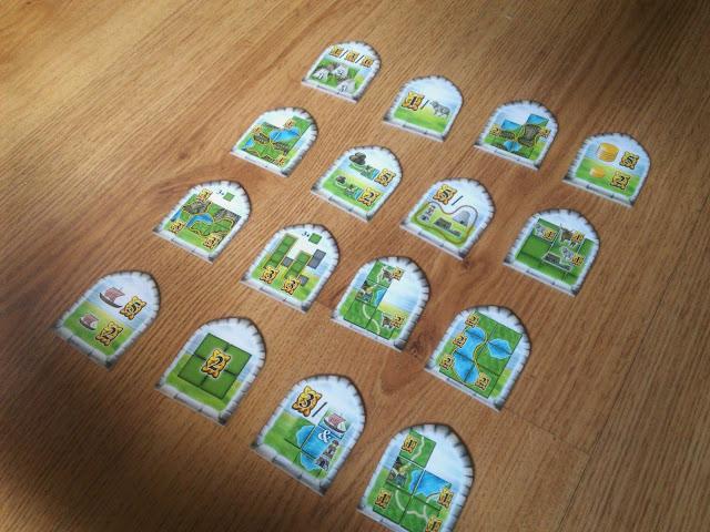 Zaczynając swoją przygodę z planszówkami nie mogło w mojej kolekcji zabraknąć klasycznego już Carcassonne, które pokazało, jak powinna wyglądać dobra gra kafelkowa. Z czasem okazało się ciut za proste i rozpocząłem poszukiwania jego następcy, który dałby mi ponowną radość z budowania królestwa. W zeszłym roku do nagrody w kategorii Zaawansowanej Gry Planszowej w Niemczech została wybrana niepozorna Wyspa Skye, konkurująca z takimi tytułami jak Pandemic: Legacy czy T.I.M.E. Stories. Musiałem się z nią zapoznać - przeczytałem instrukcję, parę recenzji i wiedziałem, że Wyspa Skye prędzej czy później znajdzie się w mojej kolekcji. Zapraszam na recenzję.   W mniejszym od standardowych, prostokątnym pudełku znajdziemy sporo dobrego. Zacznijmy od kremowego, ekologicznego (!) woreczka na kafle - to w nim będziemy trzymać większość elementów gry, gdyż Wyspa Skye nie posiada żadnej wypraski. Wiele kartonu, który trzeba wyjąć z wyprasek prezentuje się naprawdę dobrze - plansza, kafle, żetony i zasłonki zostały wydane naprawdę porządnie i nie można się do nich doczepić. Najsłabszym ogniwem całego zestawu jest średnio przejrzysta instrukcja. Od początku denerwuje mnie jej składany format, który jest średnio intuicyjny i niewygodny. Opis zasad jest co prawda podparty różnymi przykładami, ale w jej treści można znaleźć kilka nieścisłości, które trzeba rozwiązać na własną rękę, korzystając z forum na BGG lub w GF. SCD została ustalona na poziomie 99 zł i myślę, że jest to ciut za dużo, jednak pamiętajcie, żeby skorzystać z porównywarki cen - to zachęci Was do zakupu Wyspy Skye.    Grafiki przedstawione na kaflach są czytelne, choć podczas rozgrywek pojawiało się kilka pytań. Chodziło głównie o granicę między obszarami, która nie zawsze była dobrze zakończona i nie do końca było wiadomo jak punktować dany obszar. Wszystkie elementy nadrukowane na kaflach, czyli farmy, zwierzaki oraz brochy (pomijając latarnie) wyglądają nieco sztucznie, wklejone jakby z innego projektu i nie skończo