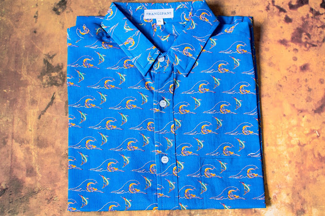 A bright blue cotton shirt folder up on a brown background. The shirt has a repeated print of waves with a dolphin or fish leaping over them. The shirt is from British designer Frangipani