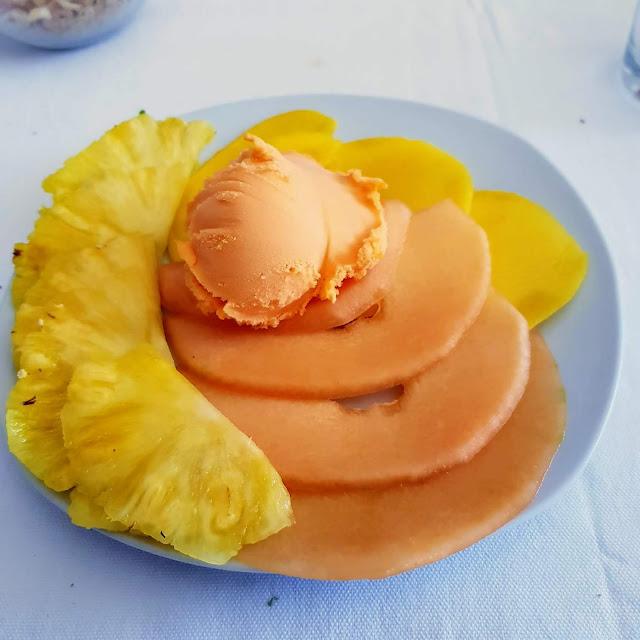 Prato de fruta fatiada, meloa e ananás, com gelado de tangerina