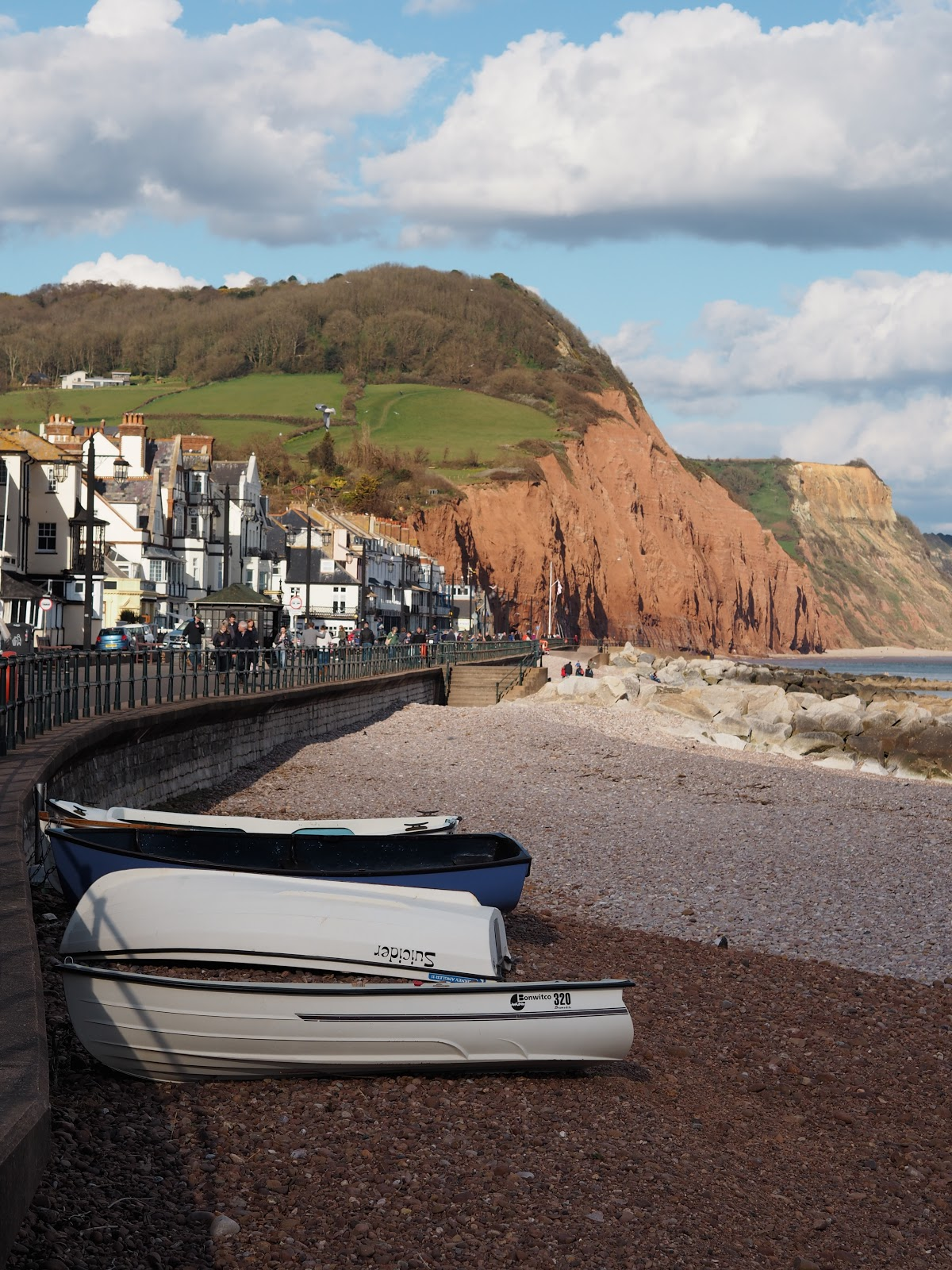 Boats on the pebble beach at Sidmouth with the Jurassic Coast behind and sea, Sidmouth, Devon