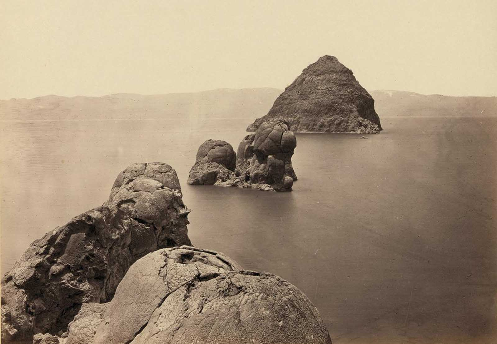 The Pyramid and Domes, a line of dome-shaped tufa rocks in Pyramid Lake, Nevada, seen in 1867.