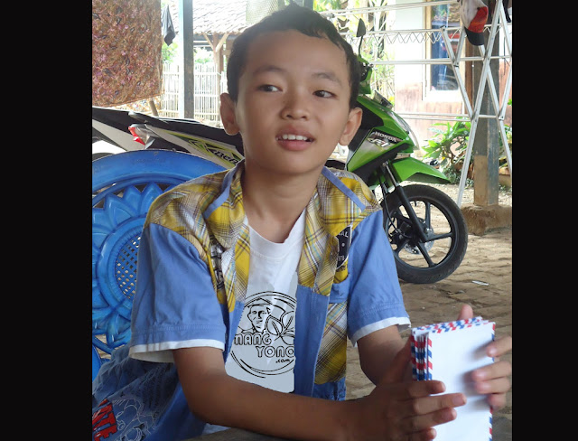 "FOTO : Si Sulung "" Gugum"" Memegang amplop berisi Uang hasil Tukar Rantang. Foto doc Mang Yono"