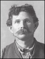 A white man in a plaid shirt and vest, looking head-on toward the camera. He has mussed short brown hair and a large mustache.