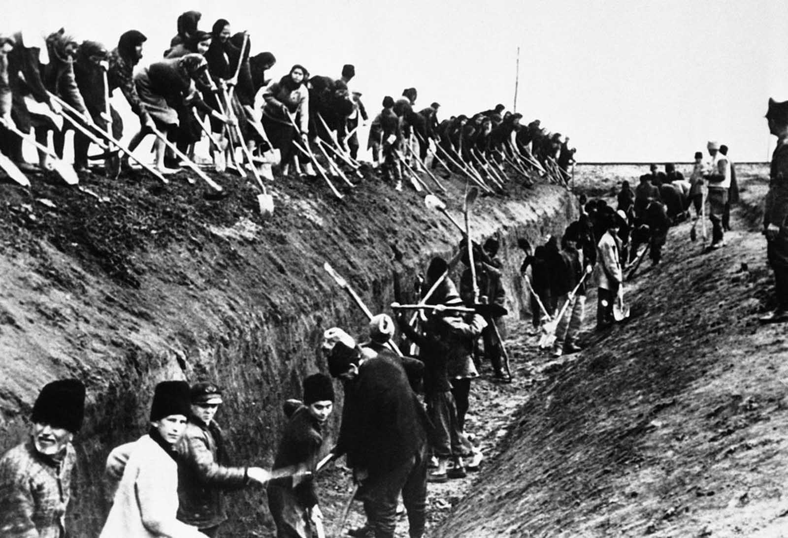An army of Romanian civilians, men and women, both young and old, dig anti-tank ditches in a border area, on June 22, 1944, in readiness to repel Soviet armies.