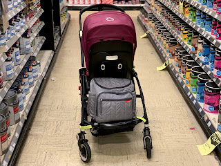 A pushchair in a DIY paint aisle with the Skip Hop changing bag on the back