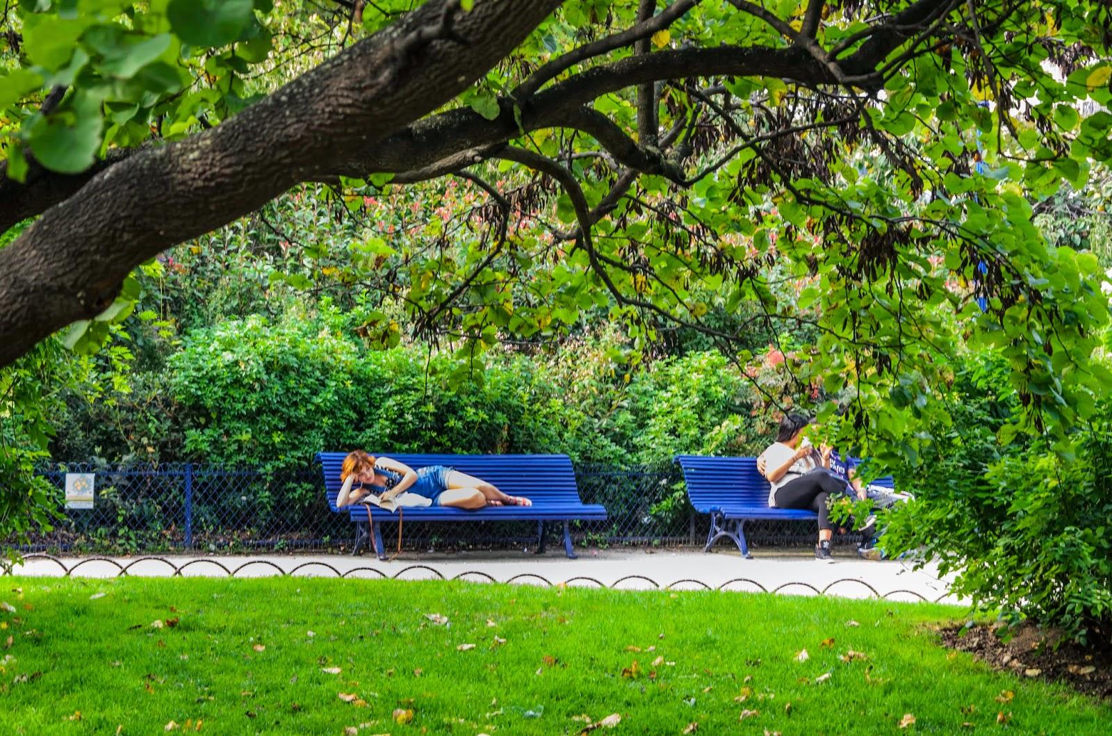 fotografia de mulher lendo deitada no banco da praça.