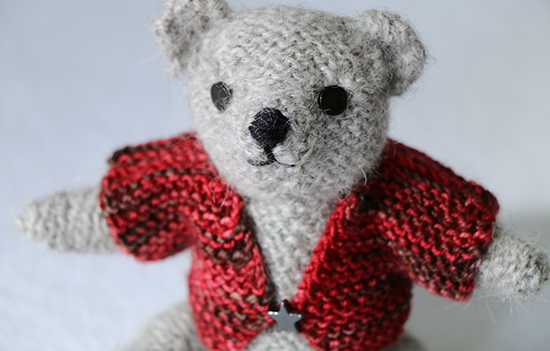 Detail of Hand Knit Light Gray Wool Teddy Wearing a Red Sweater