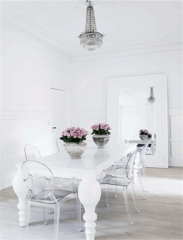 mesa comedor blanca con sillas transparentes y lampara de araña antigua chicanddeco