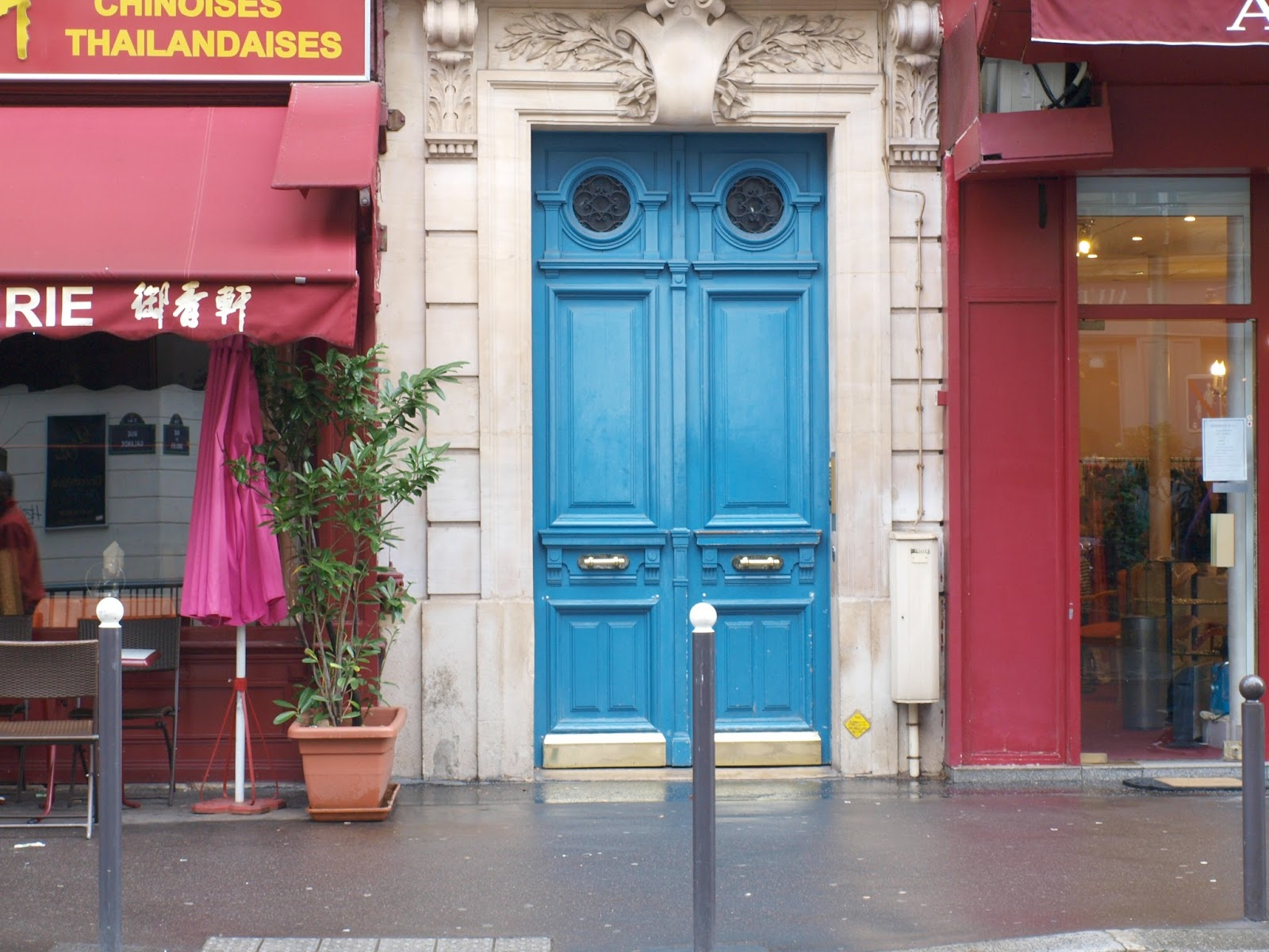 Exterior of our Paris apartment with bold blue doors and brass hardware - Hello Lovely Studio