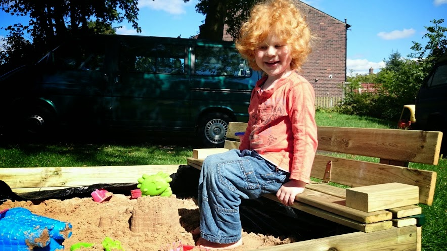4 year old sitting on bench seat on side of sand pit