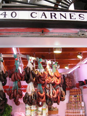Market stall 'CARNES' with hanging sausages