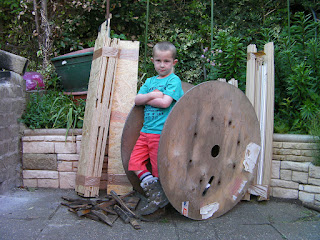 mr cool with army boots and cable drum for bonfire
