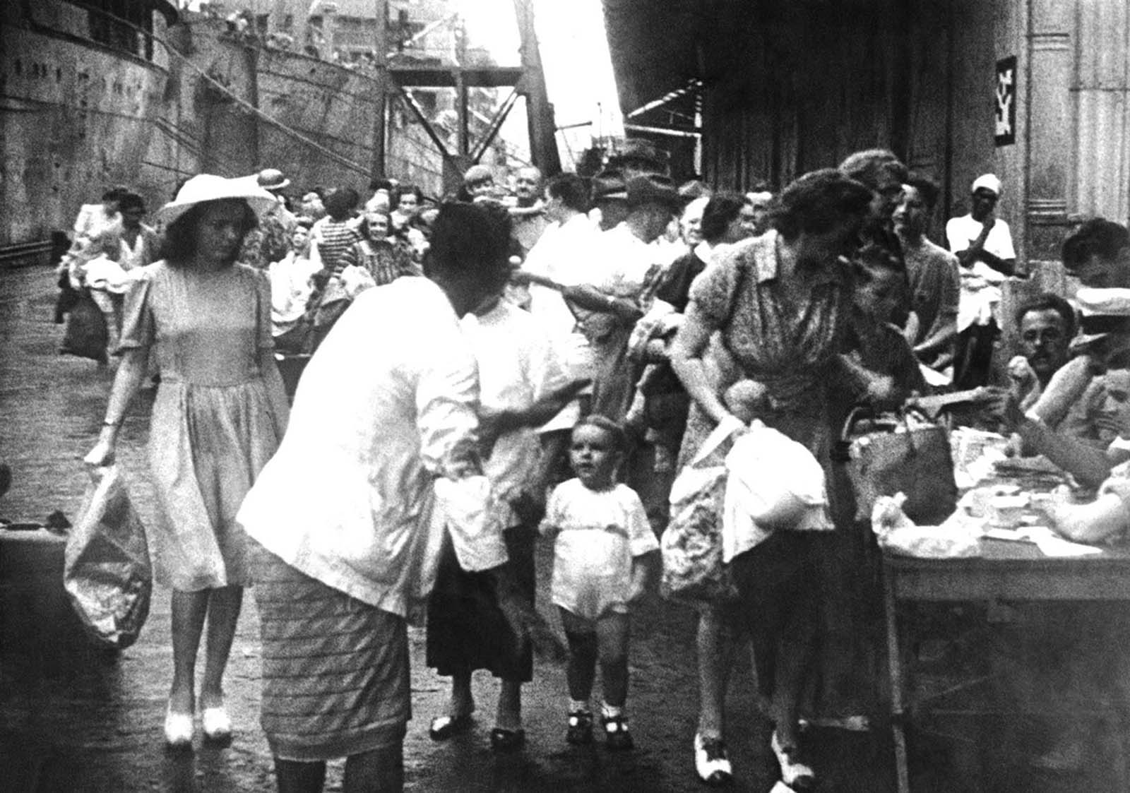 In Singapore, women and children were evacuated from the onetime British bastion before the Japanese invasion. Here, some of the women, carrying bags and paper sacks, register before boarding a waiting ship on March 9, 1942.
