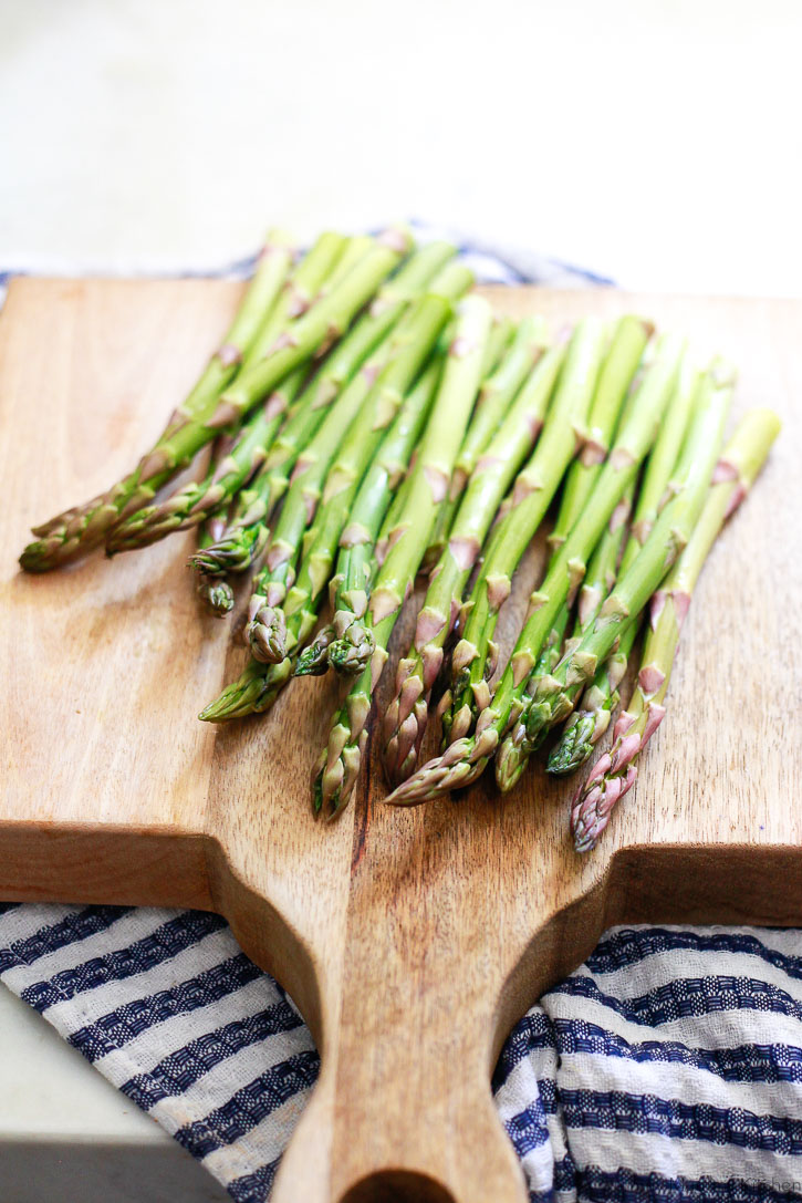 Beautiful close-up photo of green asparagus on a cutting board with a blue and white striped kitchen towel.
