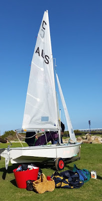 A 'Cadet' class two-person sailing boat on a trailer parked on the lawn getting ready to sail.  A bundle of buckets, bags and belongings are on the lawn inthe foreground. A white line on the horizon is the Largs Jetty.