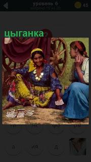 цыганка на полу гадает девушке на картах