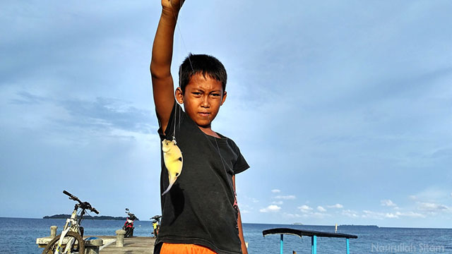 Hasan berhasil menarik ikan tangkapannya