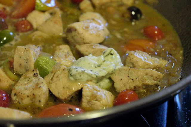 A pat of the Tuscan herb butter being added to the chicken, tomatoes, onions, and garlic.