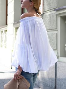 Blusa blanca con mucho vuelo y los hombros al aire