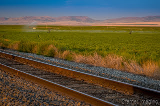 Cramer Imaging's photograph of a potato field getting watered in American Falls, Idaho with railroad tracks in front