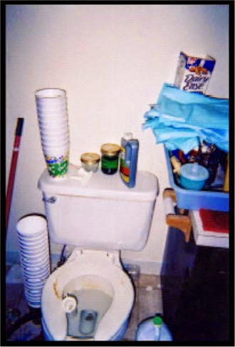 Dirty toilet with stacks of empty styrofoam cups on and beside it and assorted clutter on all sides