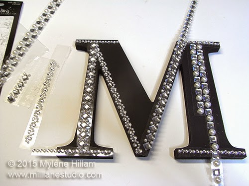 "Positioning the crystal and pearl border strips along the outlines of the ""M"""