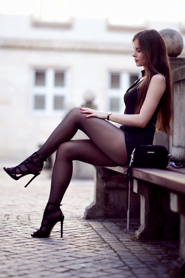 Czarny top z chokerem, zamszowe szorty, czarne rajstopy i sandały na szpilce