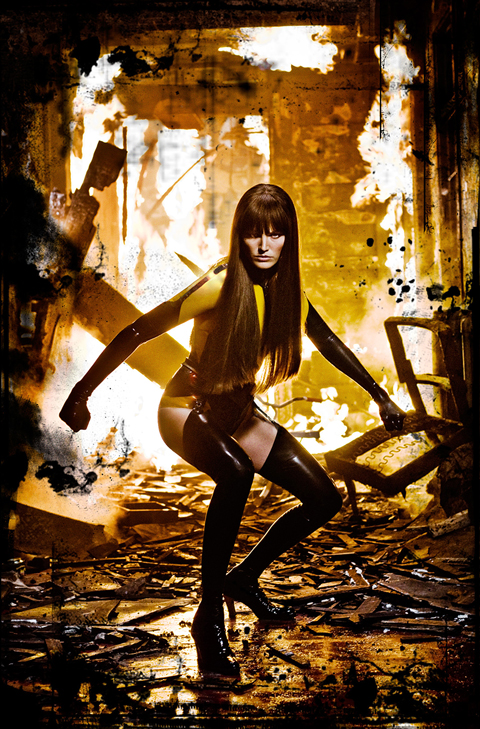 Malin Akerman in burning building catlike pose Watchmen 2009 movieloversreviews.filminspector.com
