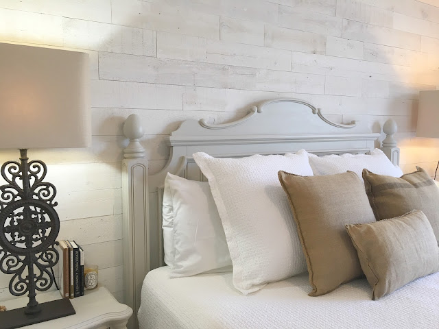 bed in front of Stikwood wood plank wall in master bedroom of Hello Lovely Studio fixer upper