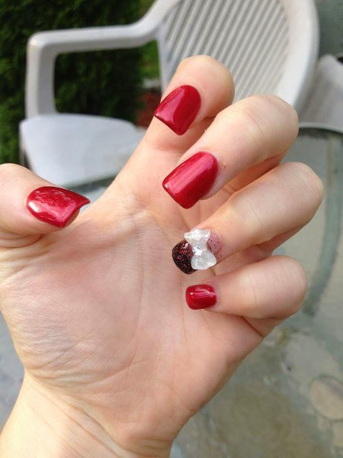 Uñas rojo diamante  y un moño blanco.