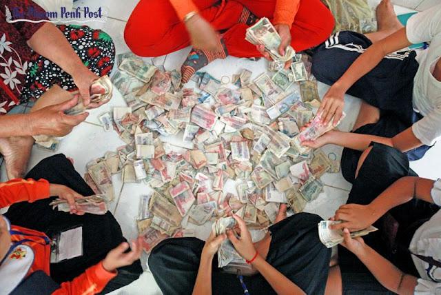 People sort riel banknotes in Phnom Penh last year. Vireak Mai