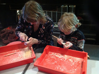 Adult and child sat at table carving soapstone over trays