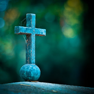 Image of an aged stone cross with a background of out-of-focus foliage.