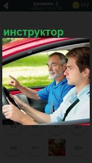 В кабине автомобиля сидят инструктор по вождению и стажер водитель